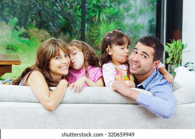 Beautiful hispanic family of four posing with heads sticking up from back of sofa looking at camera smiling.