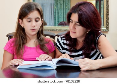 Beautiful hispanic girl and her young mother reading a book together or studying at home