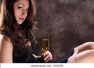A beautiful Hispanic girl relaxing with a glass of champagne. Sultry. Emotive. Room for text. Left justified.