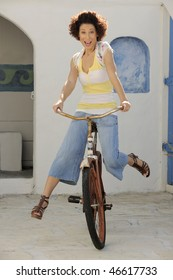 Beautiful Hispanic model riding vintage bicycle in front of white stucco wall.