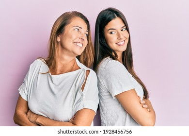 Beautiful hispanic mother and daughter smiling happy over isolated pink background.