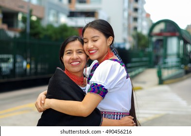 Beautiful hispanic mother and daughter wearing traditional andean clothing, waiting for bus at public station while embracing together, smiling happily, outdoors environment