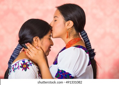 Beautiful hispanic mother and daughter wearing traditional andean clothing, seen from profile angle facing each other, young woman kissing her mom on forehead, pink studio background
