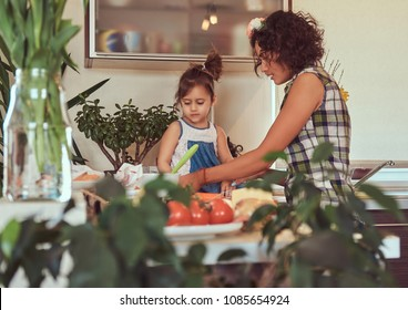 Beautiful Hispanic mother teaches her cute little daughter prepare pizza in the kitchen.