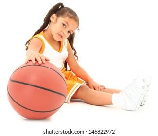 Beautiful Hispanic preschool girl with basketball in uniform. clipping path