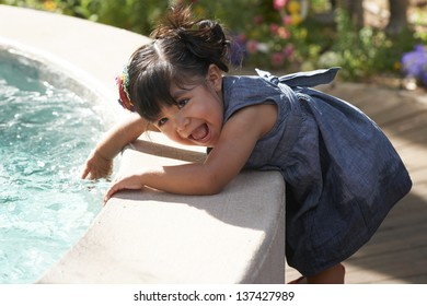 Beautiful Hispanic toddler happily playing with water from fountain.