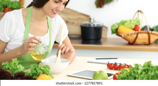 Beautiful Hispanic woman cooking in kitchen while using tablet computer and wooden spoon. Housewife found new recipe for dinner or breakfast. Healthy meal and householding concepts