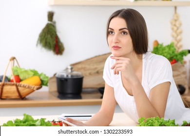 Beautiful Hispanic  woman cooking while using tablet computer in kitchen or  making online shopping by touchpad and credit card. Housewife found new recipe for dinner