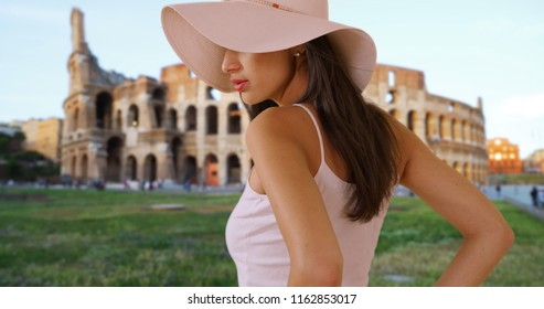 Beautiful Hispanic woman in floppy sunhat stand near Roman coliseum in Italy