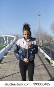 Beautiful hispanic woman getting ready for her daily workout on a bridge