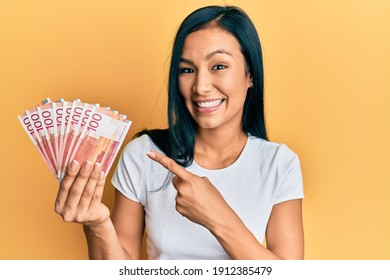 Beautiful hispanic woman holding 100 norwegian krone banknotes smiling happy pointing with hand and finger