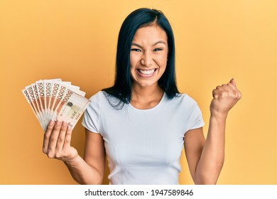 Beautiful hispanic woman holding 5000 south korean won banknotes screaming proud, celebrating victory and success very excited with raised arm