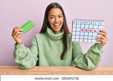 Beautiful hispanic woman holding birth control pills smiling and laughing hard out loud because funny crazy joke.