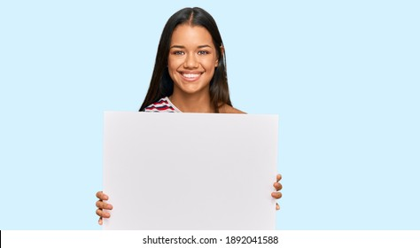 Beautiful hispanic woman holding blank empty banner looking positive and happy standing and smiling with a confident smile showing teeth
