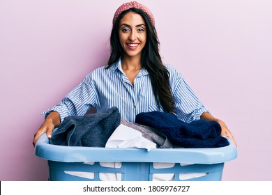 Beautiful hispanic woman holding laundry basket smiling and laughing hard out loud because funny crazy joke.