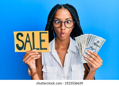 Beautiful hispanic woman holding sale banner and dollars making fish face with mouth and squinting eyes, crazy and comical.