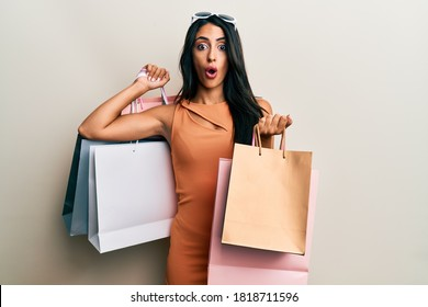 Beautiful hispanic woman holding shopping bags afraid and shocked with surprise and amazed expression, fear and excited face.