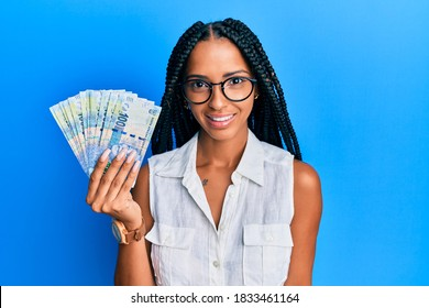 Beautiful hispanic woman holding south african 100 rand banknotes looking positive and happy standing and smiling with a confident smile showing teeth