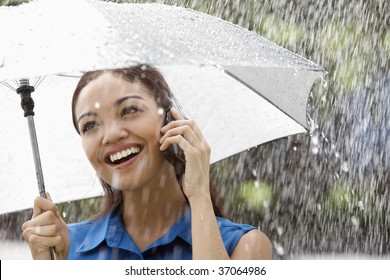 Beautiful Hispanic woman holding umbrella out in the rain talking on a cell phone