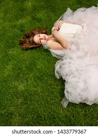 beautiful hispanic woman laying in grass with big tulle skirt