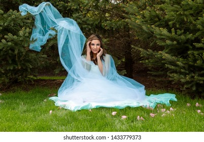 beautiful hispanic woman in pale blue dress sitting in grass