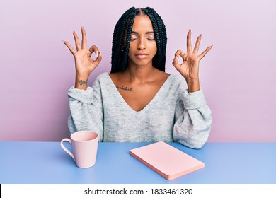 Beautiful hispanic woman reading a book and drinking a coffee relax and smiling with eyes closed doing meditation gesture with fingers. yoga concept.