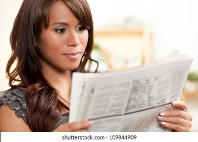 Beautiful Hispanic woman relaxing at home wearing short sleeve gray shirt and shorts.