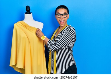 Beautiful hispanic woman with short hair standing by manikin sewing cloth celebrating crazy and amazed for success with open eyes screaming excited.