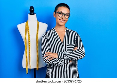 Beautiful hispanic woman with short hair standing by manikin happy face smiling with crossed arms looking at the camera. positive person.