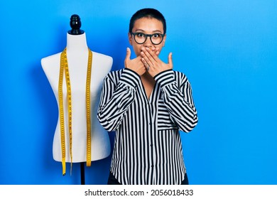 Beautiful hispanic woman with short hair standing by manikin shocked covering mouth with hands for mistake. secret concept.