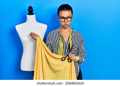 Beautiful hispanic woman with short hair standing by manikin holding cloth skeptic and nervous, frowning upset because of problem. negative person.