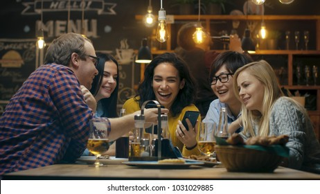 Beautiful Hispanic Woman Shows Interesting Stuff on Her Smartphone to Her Friends while They Have Good Time in Bar. They Laugh, Joke, Drink in Stylish Hipster Bar Establishment.