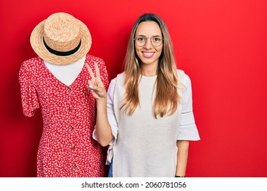 Beautiful hispanic woman standing by manikin smiling with happy face winking at the camera doing victory sign. number two.