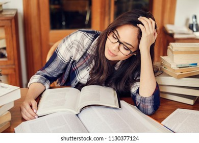 Beautiful hispanic woman student reading a book very tired, preparing for the exams