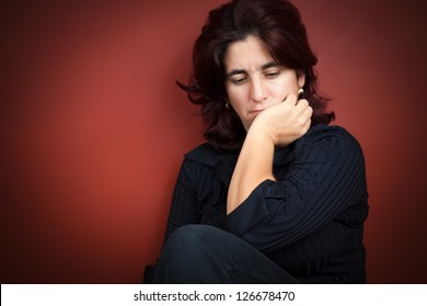 Beautiful hispanic woman with a very sad expression on a dark red background
