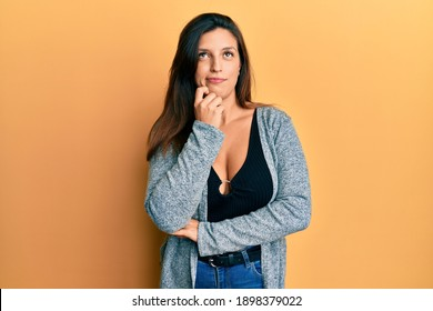 Beautiful hispanic woman wearing casual clothes thinking concentrated about doubt with finger on chin and looking up wondering