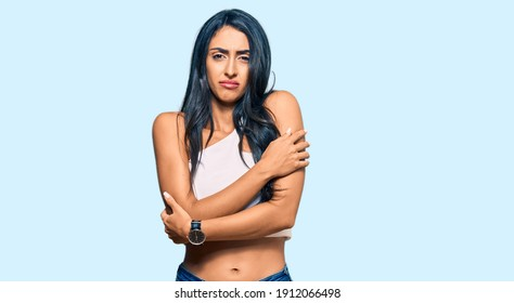 Beautiful hispanic woman wearing casual clothes shaking and freezing for winter cold with sad and shock expression on face