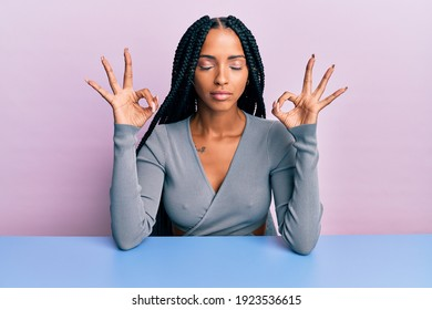 Beautiful hispanic woman wearing casual clothes sitting on the table relax and smiling with eyes closed doing meditation gesture with fingers. yoga concept.