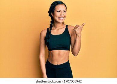 Beautiful hispanic woman wearing sportswear over yellow background pointing thumb up to the side smiling happy with open mouth