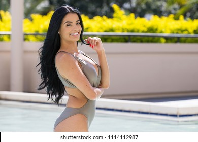 Beautiful hispanic woman wearing swim suit in pool