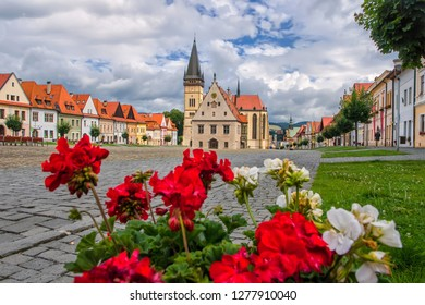 Beautiful historic town square with old building of church and colorful houses in the city Bardejov in Eastern Slovakia in Europe which is listed in UNESCO world heritage with red and white flowers