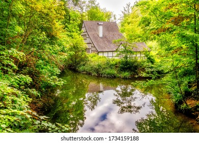 beautiful historical cultural monument halbachhammer in essen germany with green trees and reflection in a pond