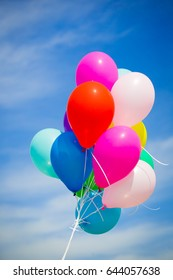 Beautiful holiday background.  Multicolored helium balloons flying in blue sky.