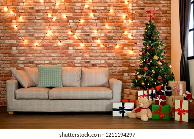 Beautiful holiday decorated living room with Christmas tree with presents under it. A cozy home lighted with numerous lights interior design ready to celebrate Xmas. New Year is coming soon.
