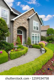 Beautiful Home Exterior with Colorful Plants, Flowers, and Green Grass. Walkway Lined by Low Lying hedges Leads to Front Door. Vertical Orientation.