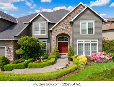 Beautiful Home Exterior with Colorful Plants, Flowers, and Green Grass. Walkway Lined by Low Lying hedges Leads to Front Door.