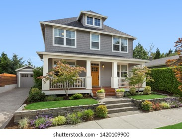 Beautiful home exterior on bright sunny day with blue sky. Home has detached garage and covered porch, with green grass and landscaping.