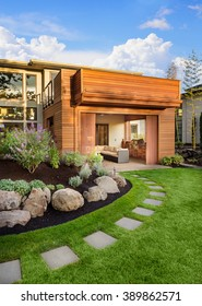 Beautiful home exterior on sunny afternoon, with green grass, walkway, elegant landscaping, covered patio with barbecue, and balcony