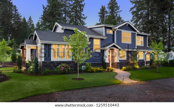 Beautiful Home Exterior at Twilight: New House with Beautiful Yard and Landscaping with Glowing Interior Lights