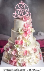 A beautiful home wedding four-tiered cake decorated with pink and green fondant handmade